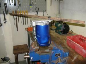 Cric installé à l'envers dans l'étau, coinçant l'écrou. Une barre en fer serre permet de donner la force nécessaire au démontage. Elle est tenue par deux simple écrous.