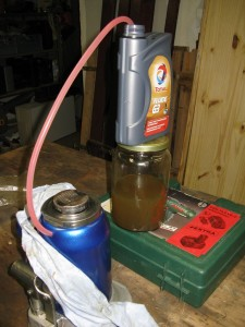 Remplissage du cric par effet siphon. L'huile (ici de l'ATF) est de couleur rouge.